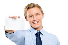 Homem de negócios novo seguro que mantém o cartaz isolado em b branco imagem de stock