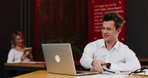 Homem de negócios novo de sorriso com laptop e papéis que chama o smartphone no escritório Termina a chamada e retorna filme