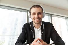 Homem de negócios novo de sorriso nos fones de ouvido que olham in camera Fotografia de Stock Royalty Free