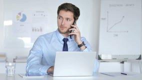 Homem de negócios novo Talking no telefone no trabalho filme