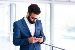 Homem de negócios novo Using Mobile Phone no local de trabalho imagem de stock royalty free