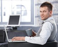 Homem de negócios ocasional com chá e portátil Fotografia de Stock Royalty Free