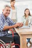 Homem de negócios ocasional na cadeira de rodas com smartphone Foto de Stock Royalty Free