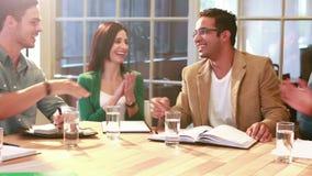 Homem de negócios ocasional que agita a mão durante a reunião
