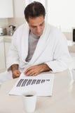 Homem de negócios ocasional que olha gráficos na cozinha Fotografia de Stock