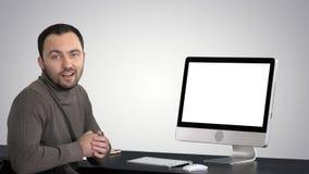 Homem de negócios ocasional que sorri e que fala na câmera que mostra algo no monitor do computador no fundo do inclinação video estoque