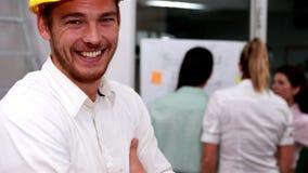 Homem de negócios ocasional que sorri na câmera com a equipe atrás dele video estoque
