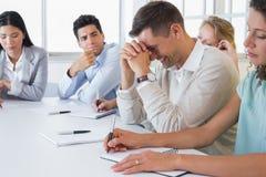 Homem de negócios ocasional que tenta não rir durante a reunião imagens de stock