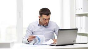 Homem de negócios ocupado com portátil e papéis no escritório filme