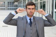 Homem de negócios ofendido que põe seus dedos sobre as orelhas Foto de Stock