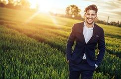 Homem de negócios otimista que relaxa no campo de trigo Fotografia de Stock