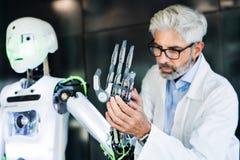 Homem de negócios ou cientista maduro com um robô imagem de stock royalty free