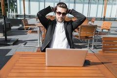 Homem de negócios ou trabalhador masculino no terno preto na tabela com smartphone imagem de stock