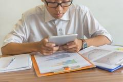 Homem de negócios de Oung que mantém seus olhos na tela da tabuleta imagem de stock royalty free