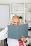 Homem de negócios Peeking Over File no escritório imagens de stock royalty free