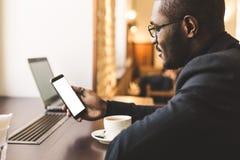 Homem de negócios de pele escura considerável novo em um café que fala em um telefone celular com um copo do chá fotos de stock royalty free