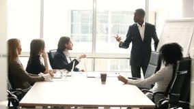 Homem de negócios de pele escura que dá a apresentação aos sócios na reunião na sala de reuniões video estoque