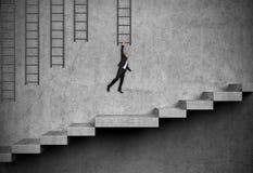 Homem de negócios pendurado na escada Fotografia de Stock