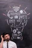 Homem de negócios pensativo com ampola pintada sobre Fotografia de Stock Royalty Free