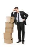 Homem de negócios pensativo com caixas de papel Imagens de Stock