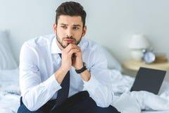 homem de negócios pensativo considerável no assento branco da camisa e do laço fotos de stock