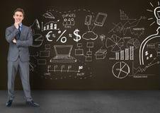 Homem de negócios pensativo que está contra símbolos do negócio no quadro-negro Foto de Stock Royalty Free
