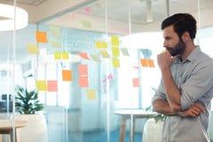Homem de negócios pensativo que olha notas adesivas no vidro Foto de Stock