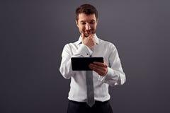 Homem de negócios que olha o PC e o sorriso da tabuleta Fotografia de Stock Royalty Free