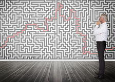 Homem de negócios pensativo que olha um labirinto em uma parede Imagens de Stock Royalty Free