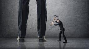 Homem de negócios pequeno que bate os pés gigantes de outros com martelo Imagens de Stock Royalty Free