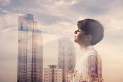 Homem de negócios pequeno que sonha para o sucesso e o arranha-céus com arquitetura da cidade Imagem de Stock