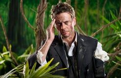 Homem de negócios perdido na selva com dor de cabeça fotografia de stock