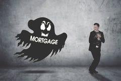 Homem de negócios perseguido por um fantasma da hipoteca imagens de stock