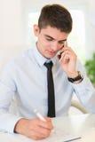 Homem de negócios Phoning In Office fotografia de stock
