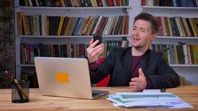 Homem de negócios positivo atrativo que manda um vídeo chamar o telefone que senta-se na frente do portátil, conversação ativa de video estoque