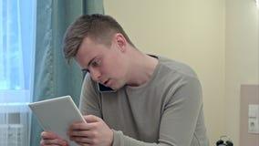 Homem de negócios preocupado na roupa ocasional que lê notícias da cama usando sua tabuleta digital e tendo um telefonema imagem de stock royalty free