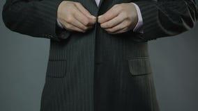 Homem de negócios presumido que abotoa seu revestimento do terno, close-up, vestuário formal vídeos de arquivo