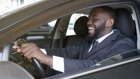Homem de negócios preto alegre que senta-se no automóvel luxuoso, movimentação do teste, transporte foto de stock