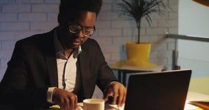 Homem de negócios preto novo cansado com o laptop e os papéis que trabalham no escritório da noite Ele que trabalha com documento filme