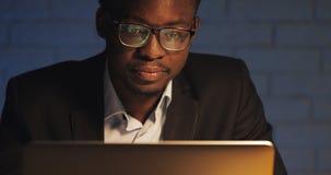 Homem de negócios preto novo cansado que trabalha com o portátil no escritório da noite Freelancer que trabalha tarde no escritór video estoque