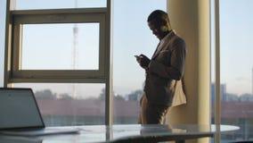 Homem de negócios preto novo no terno usando o smartphone que está pela janela no escritório no sol filme