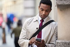 Homem de negócios preto novo que inclina-se em uma parede na rua em Londres usando o smartphone, foco seletivo, fim acima fotografia de stock