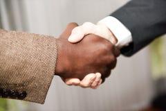 Homem de negócios preto que agita as mãos com caucasiano foto de stock