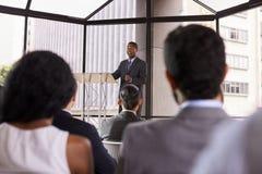 Homem de negócios preto que apresenta o seminário do negócio a uma audiência fotos de stock royalty free