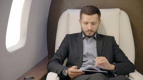 Homem de negócios principal à moda novo do diretor do banqueiro que trabalha usando o voo do durung da tabuleta no avião vídeos de arquivo