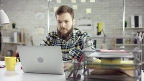 Homem de negócios produtivo que inclina o trabalho de escritório para trás de terminação no portátil, gerente eficaz satisfeito c filme