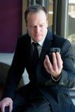 Homem de negócios profissional que olha fixamente no telefone de pilha Fotografia de Stock Royalty Free