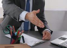 Homem de negócios pronto para agitar a mão no escritório Foto de Stock