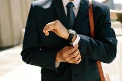 Homem de negócios que abotoa suas prateleiras da camisa que andam fora foto de stock royalty free