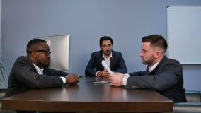 Homem de negócios que agita as mãos para selar um negócio com seu sócio durante a reunião video estoque